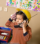 Education Preschool 3-5 year olds pretend play boy in dressup hat with pot holder on hand talking on toy telephone vertical