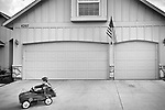 Toddler in suburban neighborhood in toy fire truck.