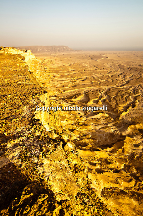 view from the edge of the shuwaymiyah plateau in southern oman, the land carved by water and wind is clearly visible and on the horizon appears the indian ocean