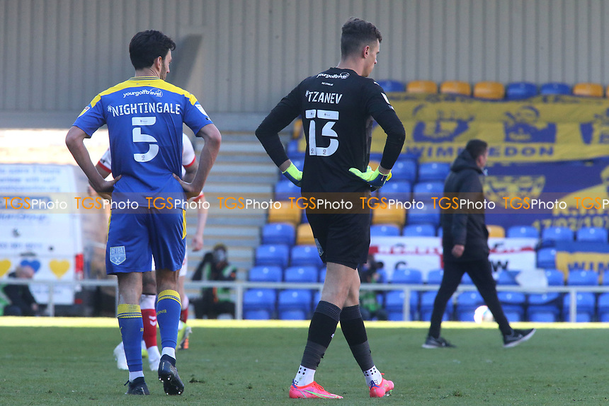 Will Nightingale and Nikola Tzanev of AFC Wimbledon show their frustration as they walk off the pitch at the end of the match after conceding a late goal during AFC Wimbledon vs Fleetwood Town, Sky Bet EFL League 1 Football at Plough Lane on 5th April 2021