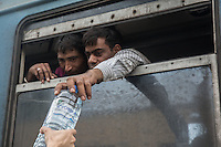 due migranti prendono una bottiglia d'acqua dal finestrino del treno<br />