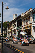 Traditional rickshaws take tourists and ride past the restored heritage houses in the UNESCO heritage town - Georgetown of Penang, Malaysia. Photo: Sanjit Das/Panos