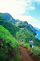 Hiker enjoys coastline views from the Kalalau Trail, an 11-mile trail along the Na Pali Coast, Kauai's remote north shoreline