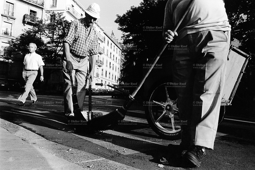 Switzerland. Geneva. Garbage collectors. Streets cleaning. Two street sweepers, their brooms and a cart. A man, wearing a white shirt, walks on the street. © 1991 Didier Ruef