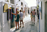 Tourists browse through art, crafts, and clothing shops in Oia, on the north point of the island of Santorini, Greece.