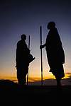 Two Masaai warriors silhouetted at sunset. Ngorongoro Conservation Area / Serengeti National Park, Tanzania. March 2014.