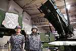 """Militaries pose for the camera next to a missile launcher at the Niconico Douga fan event in Makuhari Messe International Exhibition Hall on April 25, 2015, Chiba, Japan. The event includes special attractions such as J-pop concerts, Sumo and Pro Wrestling matches, cosplay and manga and various robot performances and is broadcast live on via the video-sharing site. Niconico Douga (in English """"Smiley, Smiley Video"""") is one of Japan's biggest video community sites where users can upload, view, share videos and write comments directly in real time, creating a sense of a shared watching. According to the organizers more than 200,000 viewers for two days will see the event by internet. The popular event is held in all 11 halls of the huge Makuhari Messe exhibition center from April 25 to 26. (Photo by Rodrigo Reyes Marin/AFLO)"""