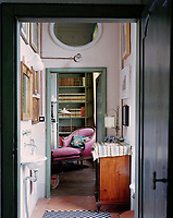 The walls of the bathroom are painted a pale pink with a view through to the master bedroom, complete with an 18th-century Piedmontese walnut chaise-longue