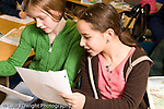 Elementary school Grade 5 two female students looking at paper together horizontal