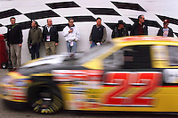 Race fans stand against a checkerboard wall watching as Ward  Burton and other NASCAR Winston Cup drivers streak by as they leave the garage area of the Daytona International Speedway in Daytona Beach, Fla., Wednesday, Feb. 13, 2002. The Twin 125 qualifying races take place Thursday for Sunday's race. (AP Photo/Daytona Beach News Journal, Kelly Jordan)