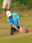 Chris Williams of England plays the ball out of the sand bunker close to the 13th green during The Senior Open Golf Tournament at The Royal Porthcawl Golf Club in South Wales this afternoon.