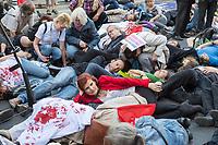"""Protest gegen die Jahreshauptversammlung des Ruestungskonzern Rheinmetall am Dienstag den 8. Mai 2018 in Berlin.<br /> Verschiedene Friedensgruppen und die Linkspartei haben zu dem Protest aufgerufen.<br /> Im Bild: Die Kundgebungsteilnehmer haben sich zu einem """"Die in"""" auf die Strasse gelegt.<br /> Vorne mit roter Jacke, Katja Kipping, Parteivorsitzende der Linkspartei.<br /> 8.5.2018, Berlin<br /> Copyright: Christian-Ditsch.de<br /> [Inhaltsveraendernde Manipulation des Fotos nur nach ausdruecklicher Genehmigung des Fotografen. Vereinbarungen ueber Abtretung von Persoenlichkeitsrechten/Model Release der abgebildeten Person/Personen liegen nicht vor. NO MODEL RELEASE! Nur fuer Redaktionelle Zwecke. Don't publish without copyright Christian-Ditsch.de, Veroeffentlichung nur mit Fotografennennung, sowie gegen Honorar, MwSt. und Beleg. Konto: I N G - D i B a, IBAN DE58500105175400192269, BIC INGDDEFFXXX, Kontakt: post@christian-ditsch.de<br /> Bei der Bearbeitung der Dateiinformationen darf die Urheberkennzeichnung in den EXIF- und  IPTC-Daten nicht entfernt werden, diese sind in digitalen Medien nach §95c UrhG rechtlich geschuetzt. Der Urhebervermerk wird gemaess §13 UrhG verlangt.]"""