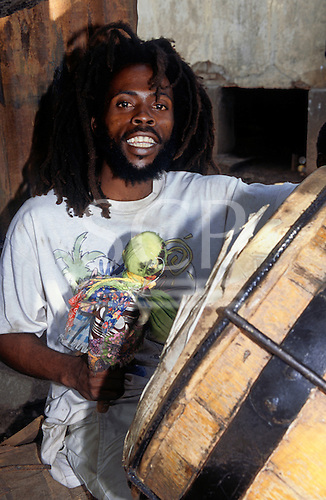 Trenchtown, Kingston, Jamaica. Rastafarian man playing a large drum.