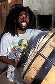 Trenchtown, Kingston, Jamaica. Rastafarian man playing a large drum.