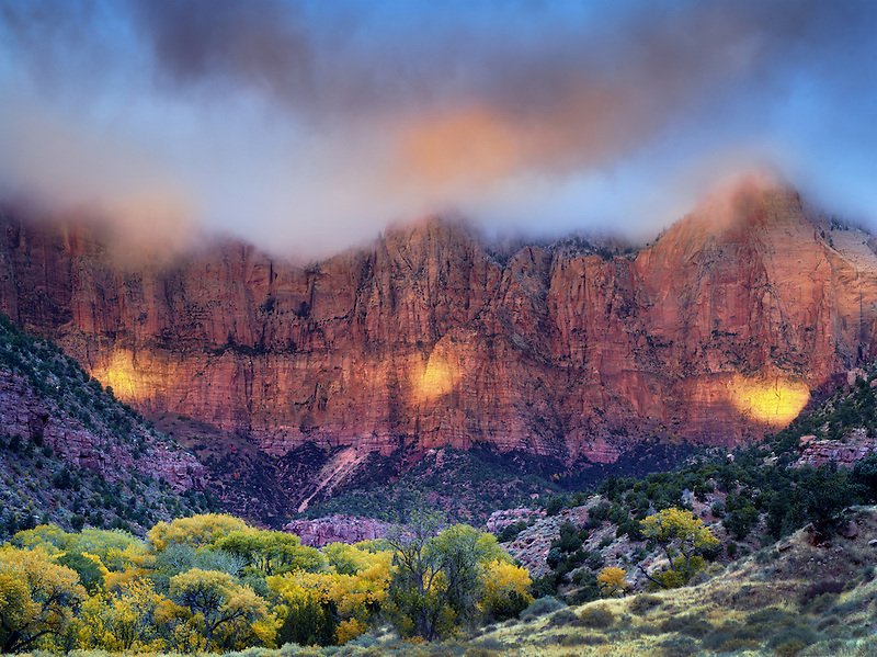 Sunrise peaking through storm clouds.with fall color Towers of the Virgin. Zion National Park, Utah