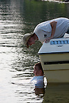 Boating accident victim in the water being checked on by another person