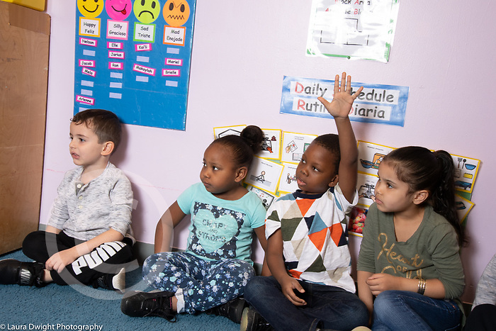 Education Childcare 4 year olds morning meeting time, boy raising hand to answer question