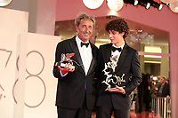 """VENICE, ITALY - SEPTEMBER 11: Director Paolo Sorrentino and Filippo Scotti pose with the Silver Lion Grand Jury Prize and the Marcello Mastroianni Award for Best New Young Actor for """"The Hand Of God"""" at the awards winner photocall during the 78th Venice International Film Festival on September 11, 2021 in Venice, Italy."""