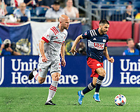 FOXBOROUGH, MA - JULY 7: Carles Gil #22 of New England Revolution brings the ball forward as Michael Bradley #4 of Toronto FC closes during a game between Toronto FC and New England Revolution at Gillette Stadium on July 7, 2021 in Foxborough, Massachusetts.