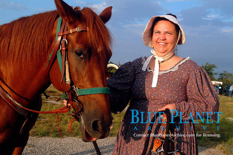 Woman wearing traditional Texan clothes taking care of her horse, Equus ferus caballus, during the annual trailride 'The Great Western Cattle Trail' in Bandera, South of Texas, USA, United States. The Great Western Cattle Trail - also known as the Dodge City Trail and the Old Texas Trail was known for cattle drives including Longhorns to the markets in the eastern part of the USA. The trail began in Bandera County, Texas and ended in Dodge City, Kansas. The entire trail extended from southern Texas to the Canadian border.