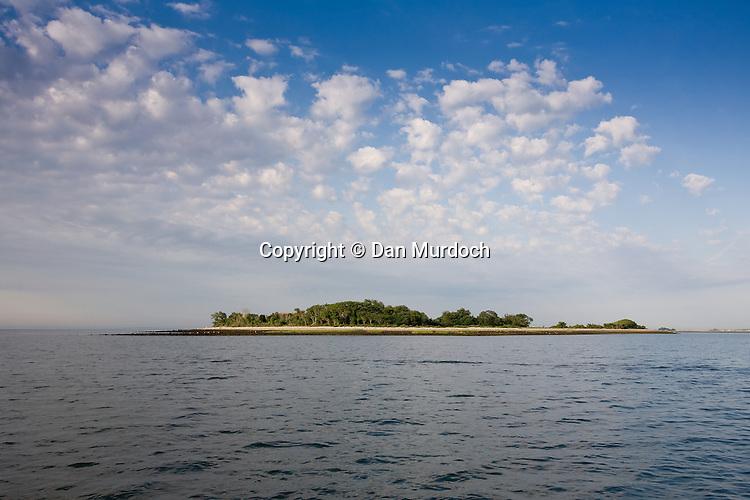 an island under puffy white clouds