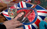 Tourist hold a drinks and a flag as they look for Kate and Prince William as they Royal party come down the mall in London. .Picture: Maurice McDonald/Universal News And Sport (Europe).29 April 2011..