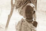 """A girl grows up in a dusty cattle camp near Rumbek, South Sudan.  The Dinka are traditionally """"cattle keepers,"""" living in cattle camps with hundreds or even thousands of cows."""