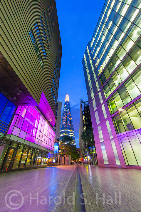 The 87 story London Shard of glass is seen from City Hall plaza at dusk.  A small stream of water flows through the pedestrian walkway around City Hall.