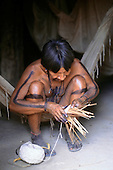 Asurini Indians, Amazon, Brazil.  Man in hammock, making artifacts with string and cane.