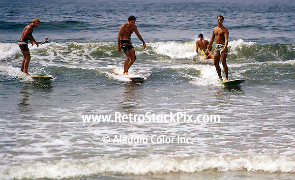 Teenagers surfing on long boards off the Cape May, NJ beach.