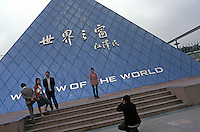 Chinese tourists take picture in front of the Musee du Louvre at Windows of the World amusement park in Shenzhen, China. The amusement park has copied many of the worlds most famous monuments and attractions, mostly in minature and attracts millions of tourists annually.