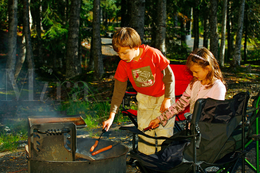Roasting hotdogs at family picnic at Trail Lake Campground, Kenai Peninsula, Chugach National Forest, Alaska.