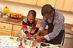 4 year old boy in kitchen with father learning to cook learning to use can opener