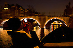 A woman takes a picture while in a boat sailing on the canals at night in Amsterdam, the Netherlands.