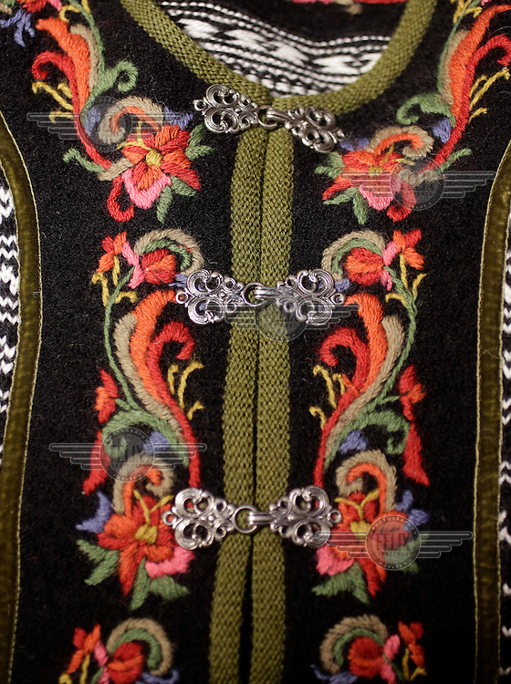"""Detail from a """"lusekofte"""", a traditional Norwegian sweater, dating from the 19th century...The lusekofte features a black and white design, and the name means """"lice jacket"""", after the isolated black stitches. It is more formally called a setesdalsgenser (a Setesdal sweater). They may also feature selburose designs. In recent times additional color is sometimes given to this black and white sweater by woven ribbons or bands of black woolen fabric embroidered in the type of colorful designs also found in the bunads and in rosemaling around the neck and along the front opening. These front opening are usually closed by a row of pewter or silver clasps."""