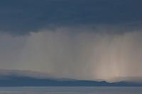 Regen über dem Meer, Unwetter, Wetter, Gewitter, Regenschauer, Schauer, Wolken, Wolke, Regenwolke, Regenwolken, Regenfront, Unwetterfront, Regen unter den dunklen Wolken wird von der Sonne angestrahlt