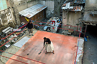 28 year old wrestler Yolanda La Amorosa (fighting name), Veraluz Cortez (real name) helps to construct a practice ring at the back of a fellow wrestler's house. Veraluz is a Cholita, a wrestler of native Aymara descent. When Cholitas fight they wear traditional costume. Veraluz fights with the lucha libre (free wrestling) group Los Diosas del Ring. ..