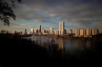 Rolling clouds pass through downtown Austin as the sunset set falls on the new Austin Skyline from Travis Heights behind the waters of beautiful Lady Bird Lake
