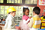 Education Preschool 3-4 year olds two boys and a girl playing dressup in kitchen family area