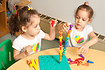 Education Preschool 3 year olds identical twin girls building peg towers using opposite dominant hand (right or left hand)