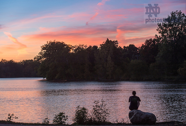 October 17, 2016; A student watches the sunset from the shore of St. Mary's Lake.  (Photo by Barbara Johnston/University of Notre Dame)