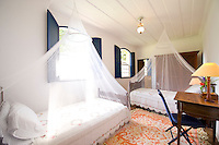 Private home in Parati Brazil. Interior of childern's room with two single beds with mosquito nets around.