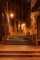 Narrow alley and steps illuminated by street lamps at night, Madrid, Spain