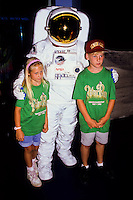 Astronaut in spacesuit posing with two children visitors at the smithsonean museum in Washington DC, USA