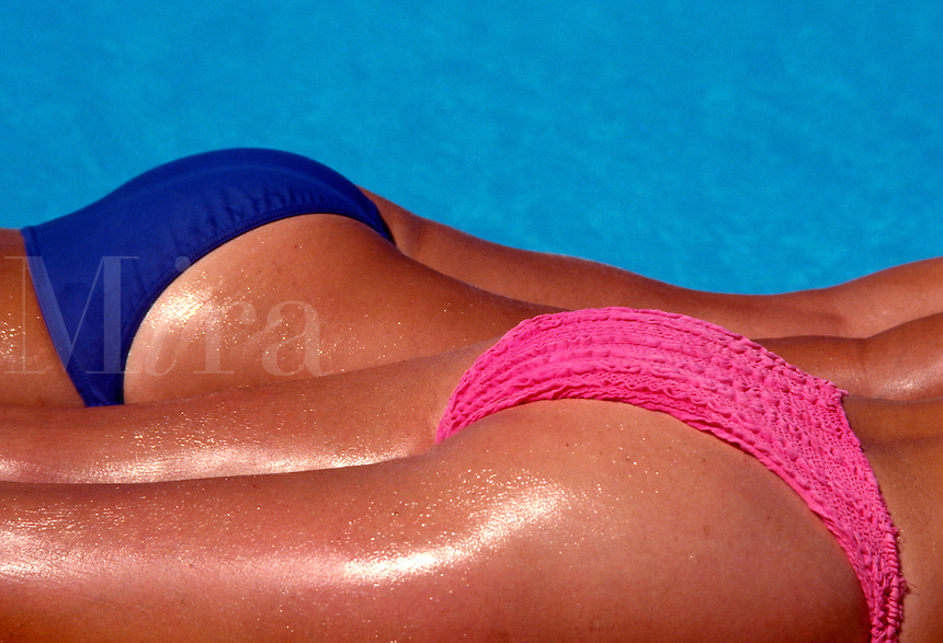Blue and pink bikini bottoms on two women sunbathers poolside.   Model Released..