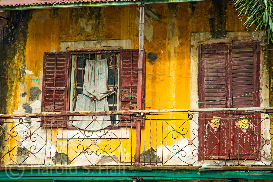The back of an old run-down resident in Macow, China.  The yellow and green colors are very common in the Portuguese type buildings.