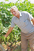 Gezim Coku, agronomist and vineyard manager. In the vineyard showing a bunch of grapes. Parellada grape variety (big leaves). Kantina Miqesia or Medaur winery, Koplik. Albania, Balkan, Europe.