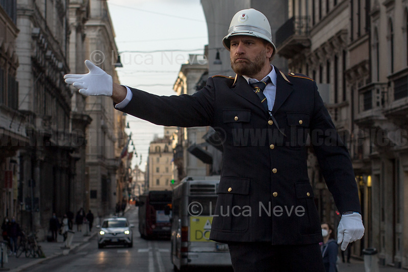 "Rome, Italy. 26th Mar, 2021. Documenting the return of the ""Vigile"", the Traffic Officer, member of the Rome Municipal Police Force (1.), directing the traffic from his historic and iconic pedestal in Piazza Venezia (2.), definitely one of the most chaotic and famous landmark of the Eternal City. <br />