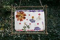 Kinder basteln ein Fensterbild mit Blüten, fertiges Fensterbild mit durchscheinenden Blüten hängt am Fenster