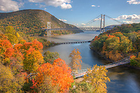 Autumn view of Bear Mountain Bridge in the distance with the CSX railroad bridge and the Popolopen Creek Suspension Footbridge in the foreground